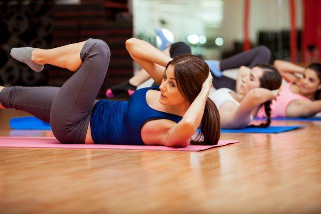 A group of women do an ab workout in a fitness studio.