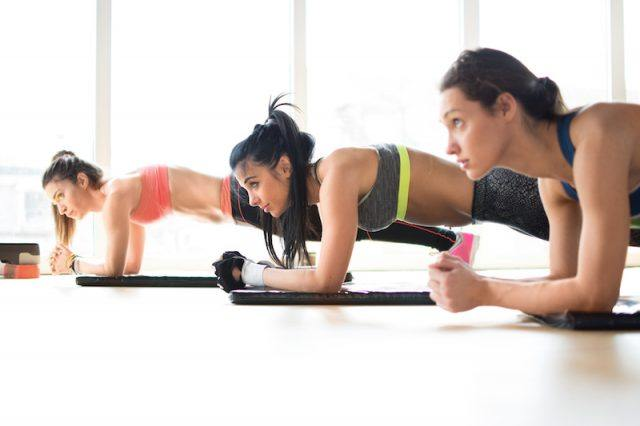 three women doing plank exercise in fitness class.