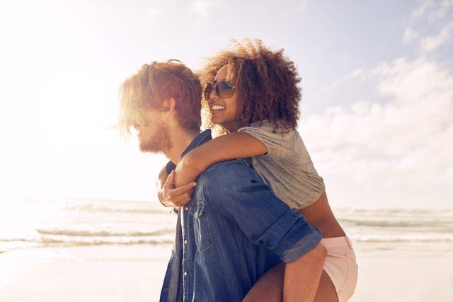 Young man carrying his girlfriend on his back at the beach.