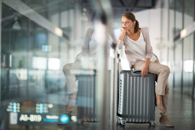 woman sitting on her suitcase looking bored at the airport