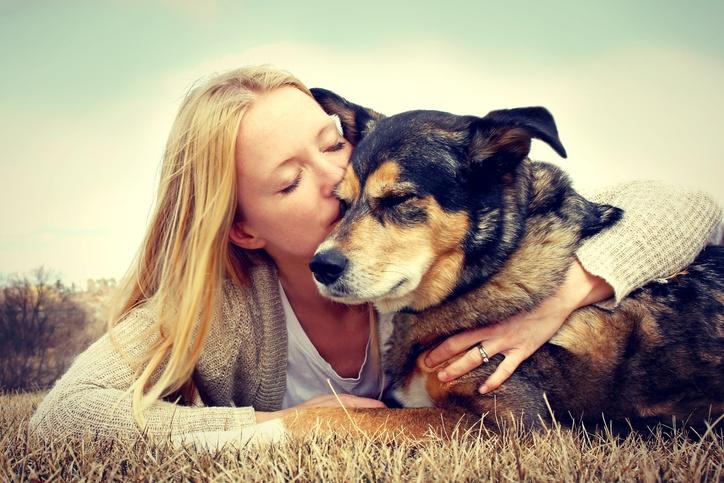Young woman hugging and kissing German Shepherd