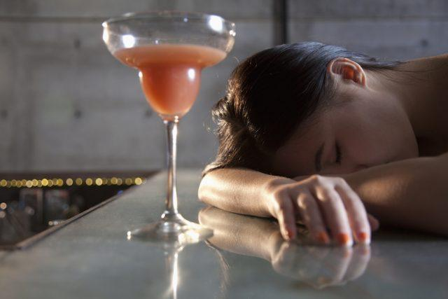 Young woman passed out on bar counter.