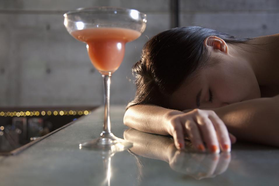 Young woman passed out on bar counter
