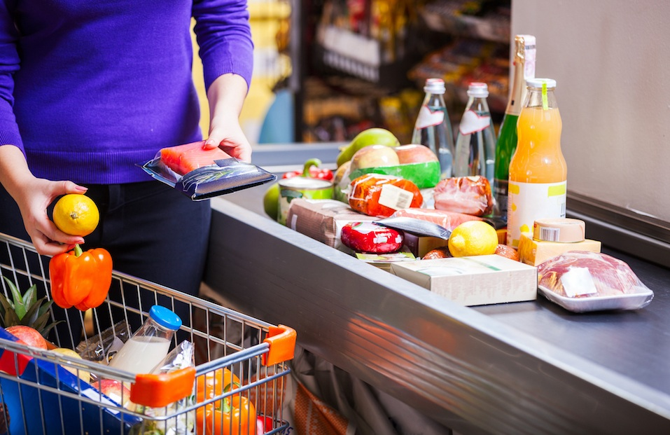 Young woman putting goods on counter in supermarket