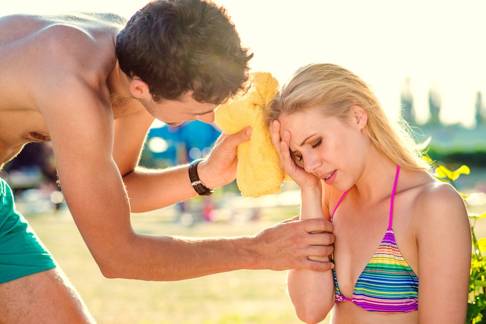 Young woman with heatstroke on a beach