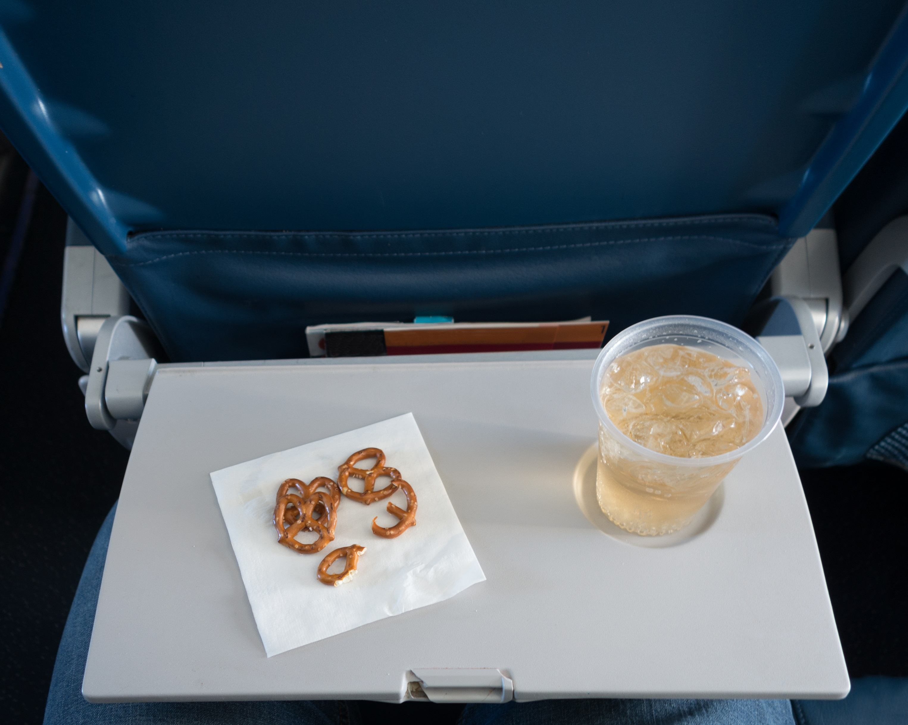 Tray table with pretzels and beverage