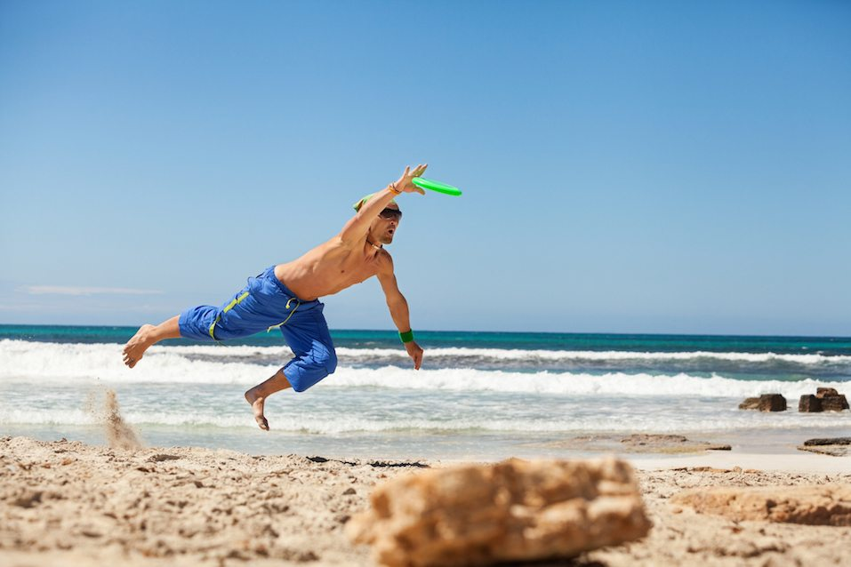 attractive man playing frisby on beach in summer