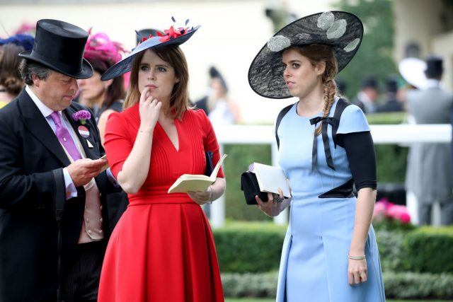 Princess Eugenie of York and Princess Beatrice of York stand while watching a parade.