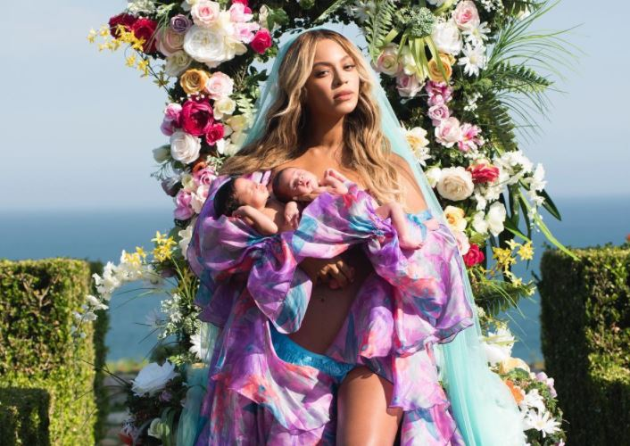 Beyoncé standing in front of flowers holding her twin babies