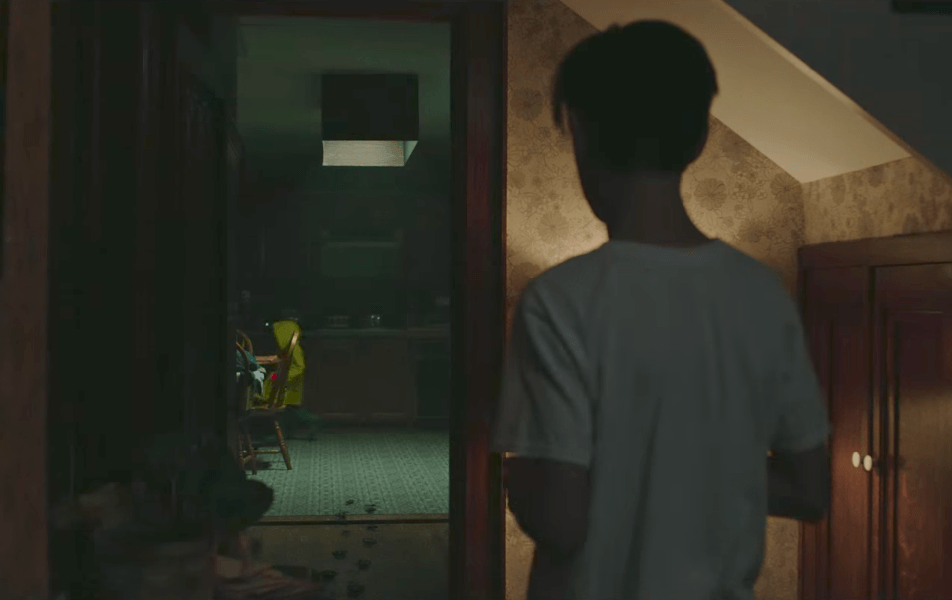 A boy in a white shirt follows a younger boy in a yellow raincoat