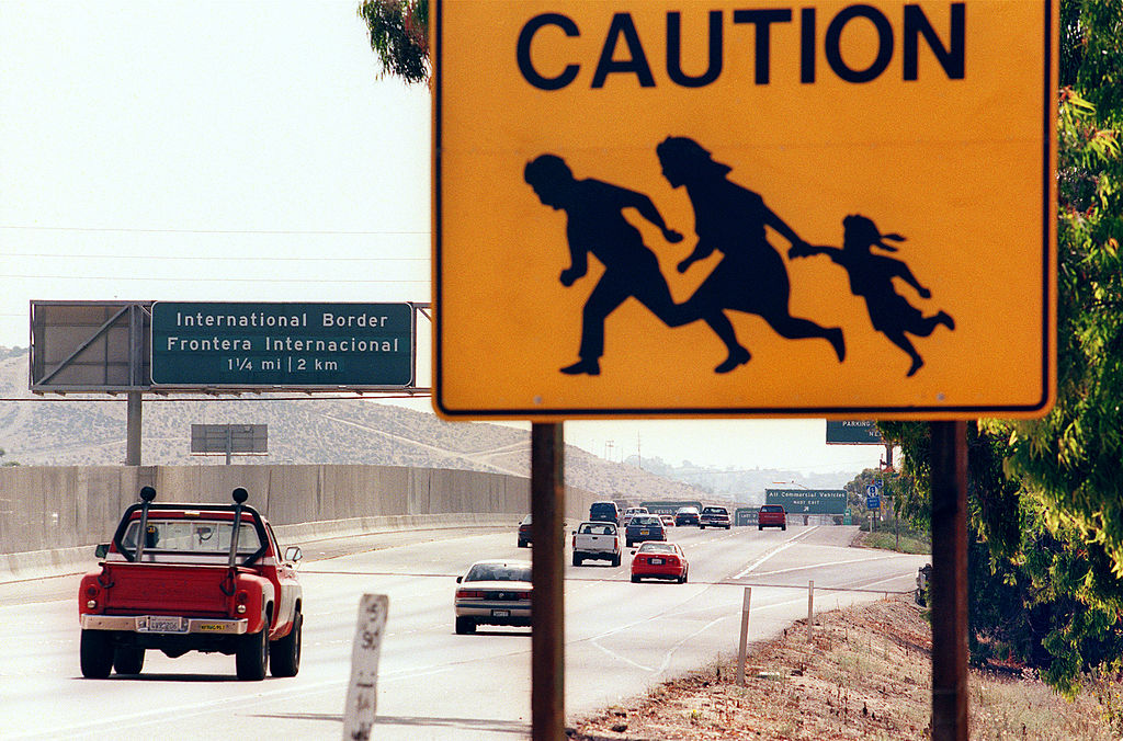A sign warning drivers about pedestrians running across the highway