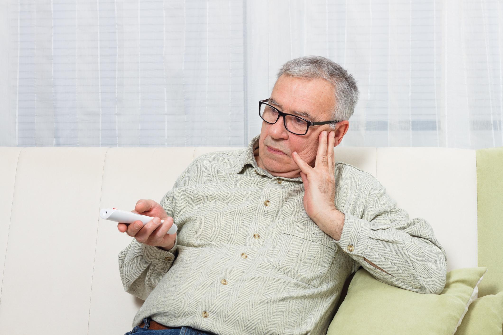 Bored senior man watching tv