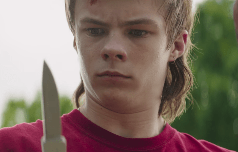 A boy in a red shirt holds up a knife
