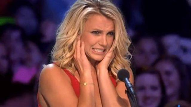 Britney Spears covering her ears while sitting in front of a microphone.