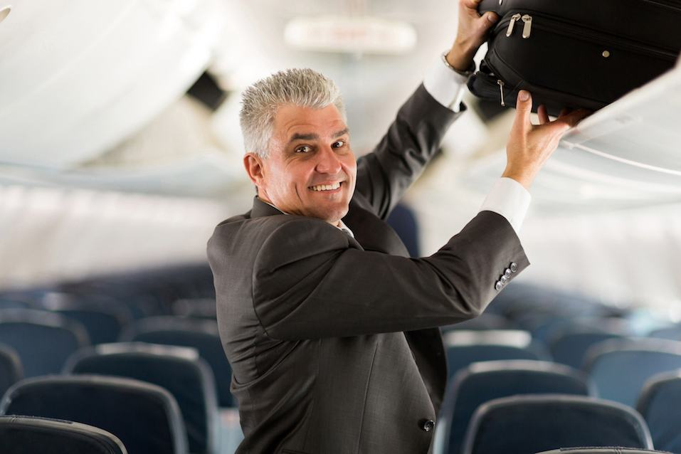 business traveler putting luggage into overhead locker on airplane