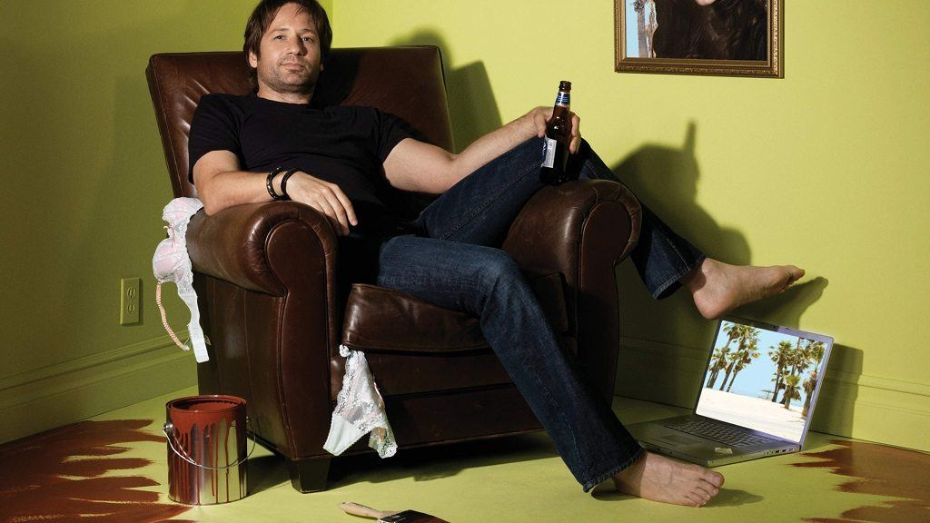 Hank Moody in a chair holding a beer with his feet on his laptop