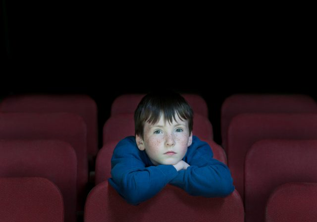 child watching a movie in a theater