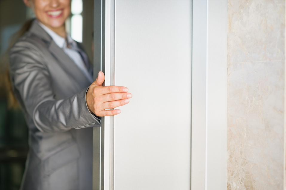 Business woman hand holding elevator door