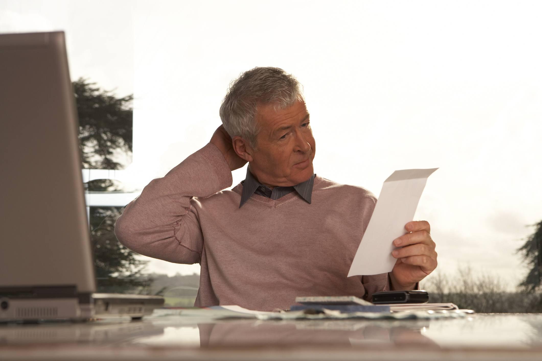 Confused older man at a desk