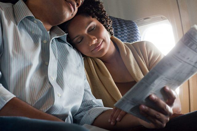 Woman sleeps on her partner's shoulder as he reads a paper.