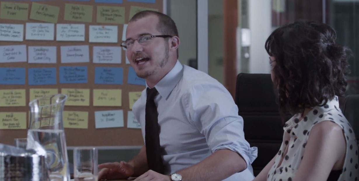 A screenshot of a man and a woman in a writer's room.