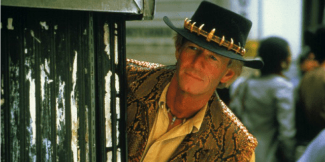 Crocodile Dundee is leaning to the side looking towards something in front of him.