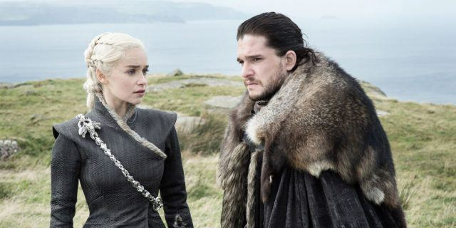 Daenerys and Jon Snow stand next to each other as they talk on a mountain top.