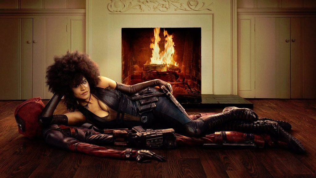 Domino laying on Deadpool as though he were a rug in front of a fireplace