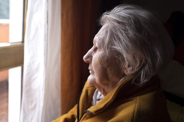 senior woman looking out window