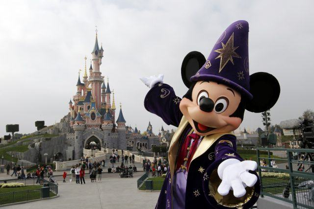Mickie poses with Sleeping Beauty's Castle