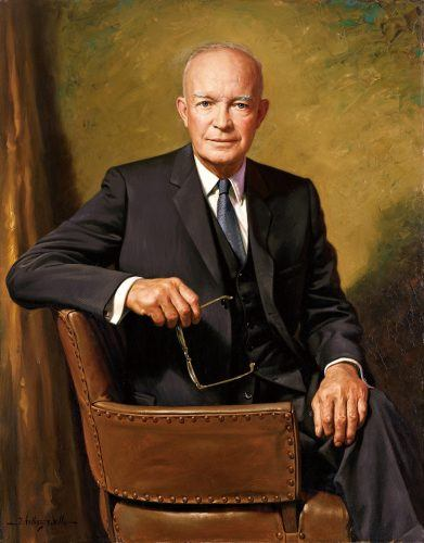 Dwight D. Eisenhower sitting on an armchair and holding his glasses.