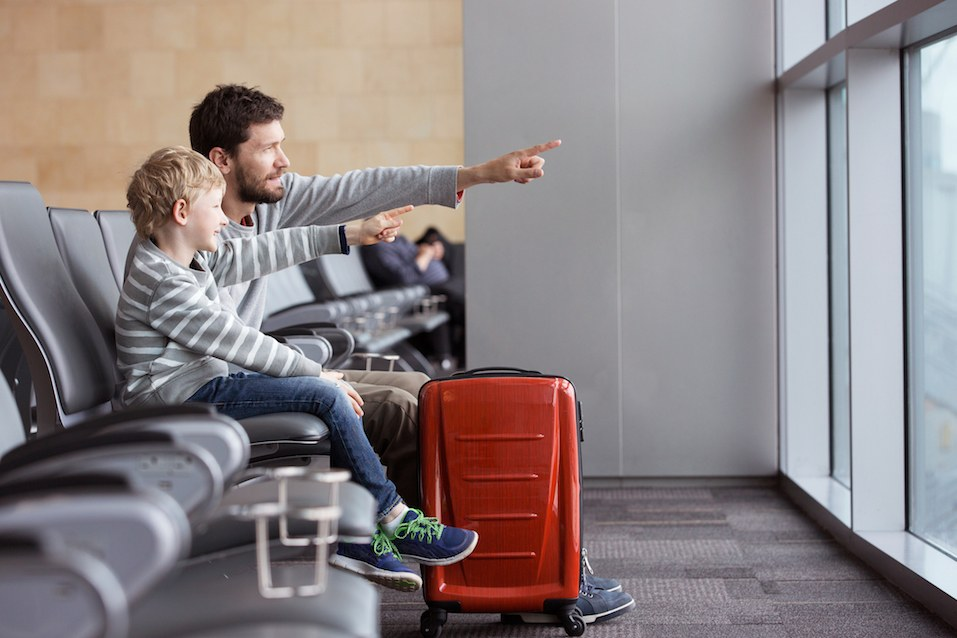 boy and his father waiting at the airport for plane departure