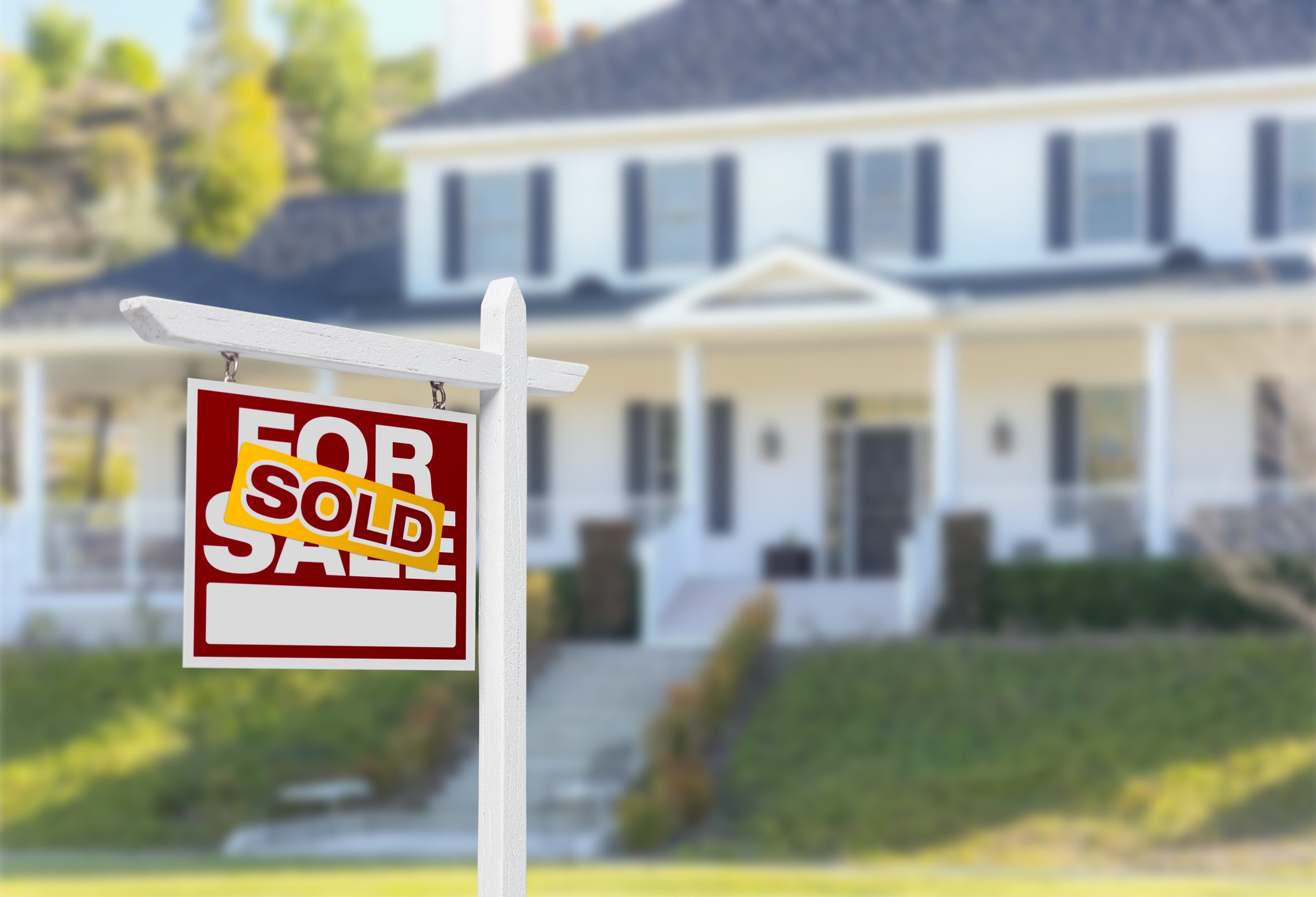 House with yellow sold sign