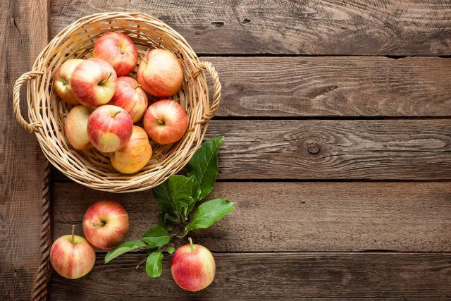 Fresh apples in wicker basket on wooden table.