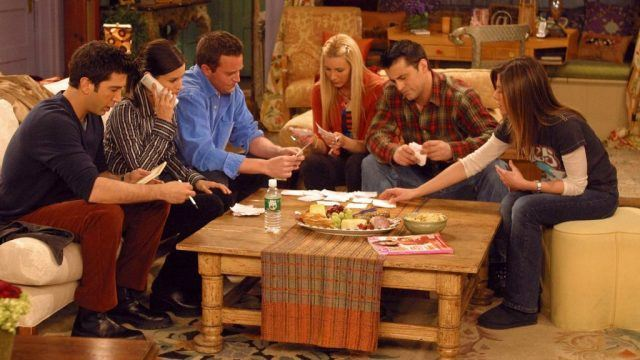 The 'Friends' gang hanging around wooden table in Monica's living room.