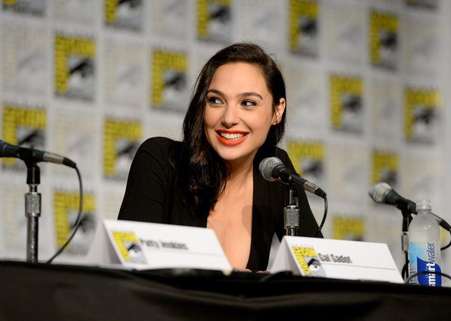 Gal Gadot at San Diego Comic Con, smiling and speaking into a microphone while sitting at a panel discussion.