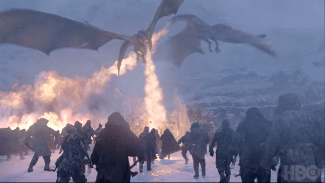 A dragon breaths fire onto an army of people