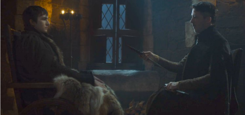 Bran and Littlefinger are seated across from each other and Littlefinger is handing Bran a dagger.