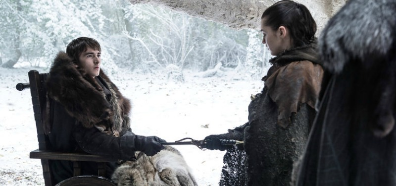 Bran is in a chair handing Arya a dagger as they're outside in the snow.