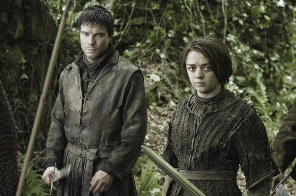 Gendry and Arya Stark stand next to each other in a wooded area