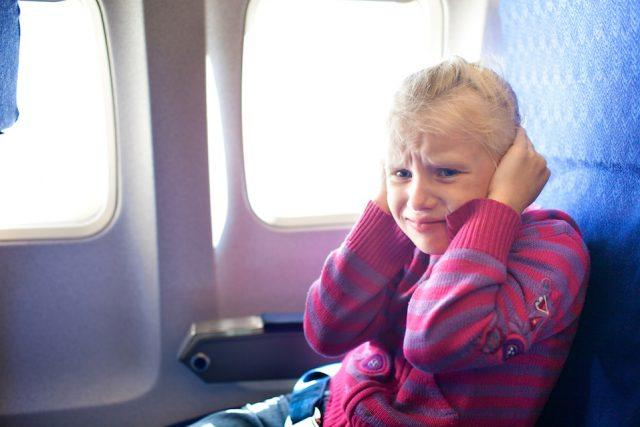girl closing ears in the airplane