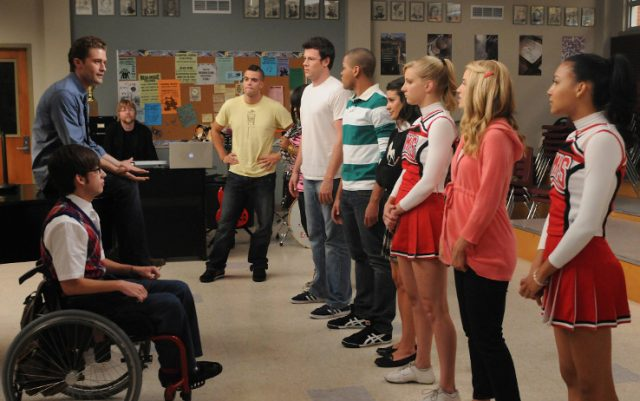 A group of students in a classroom standing next to one another across from a teacher and a boy in a wheelchair