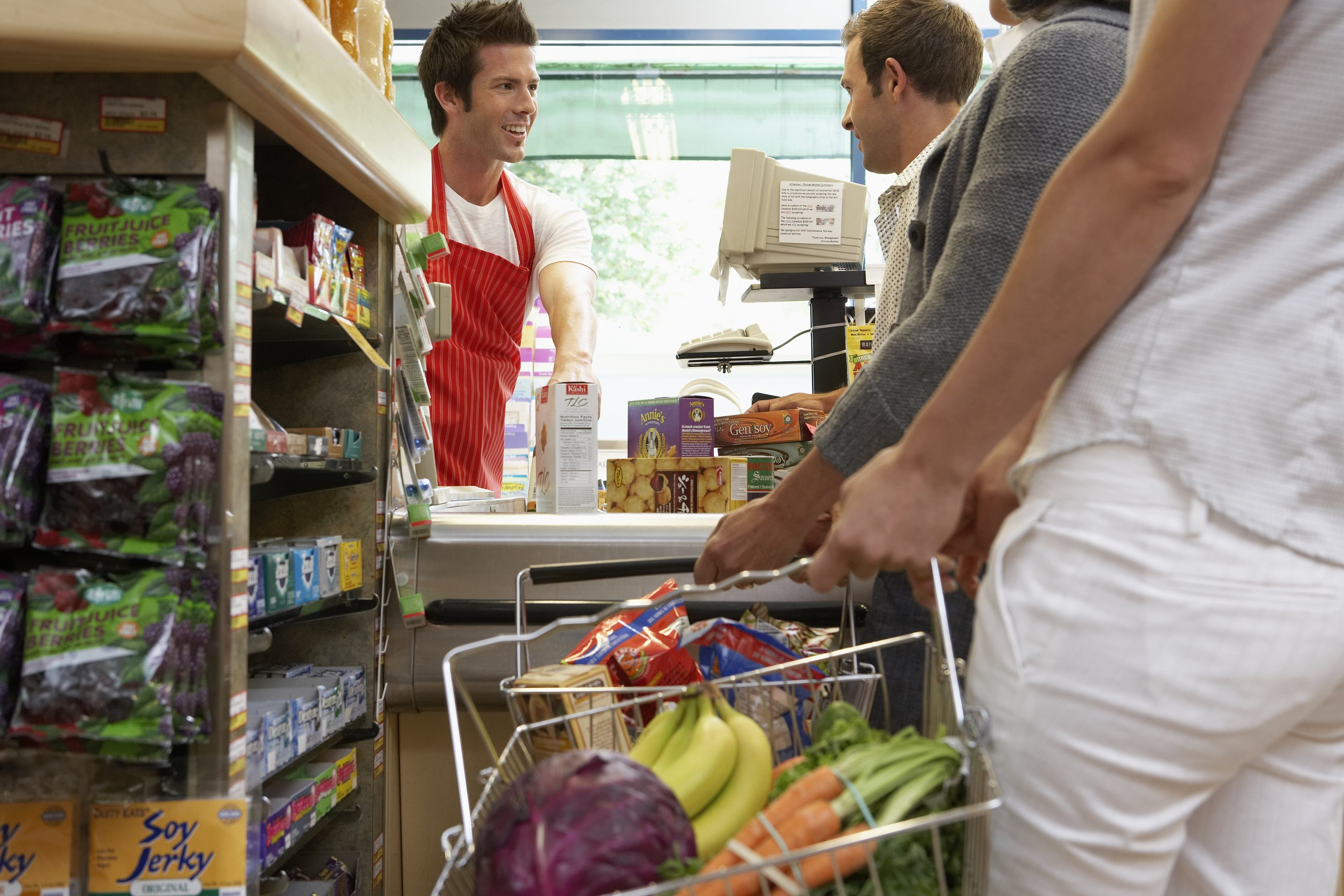 Male cashier with customers