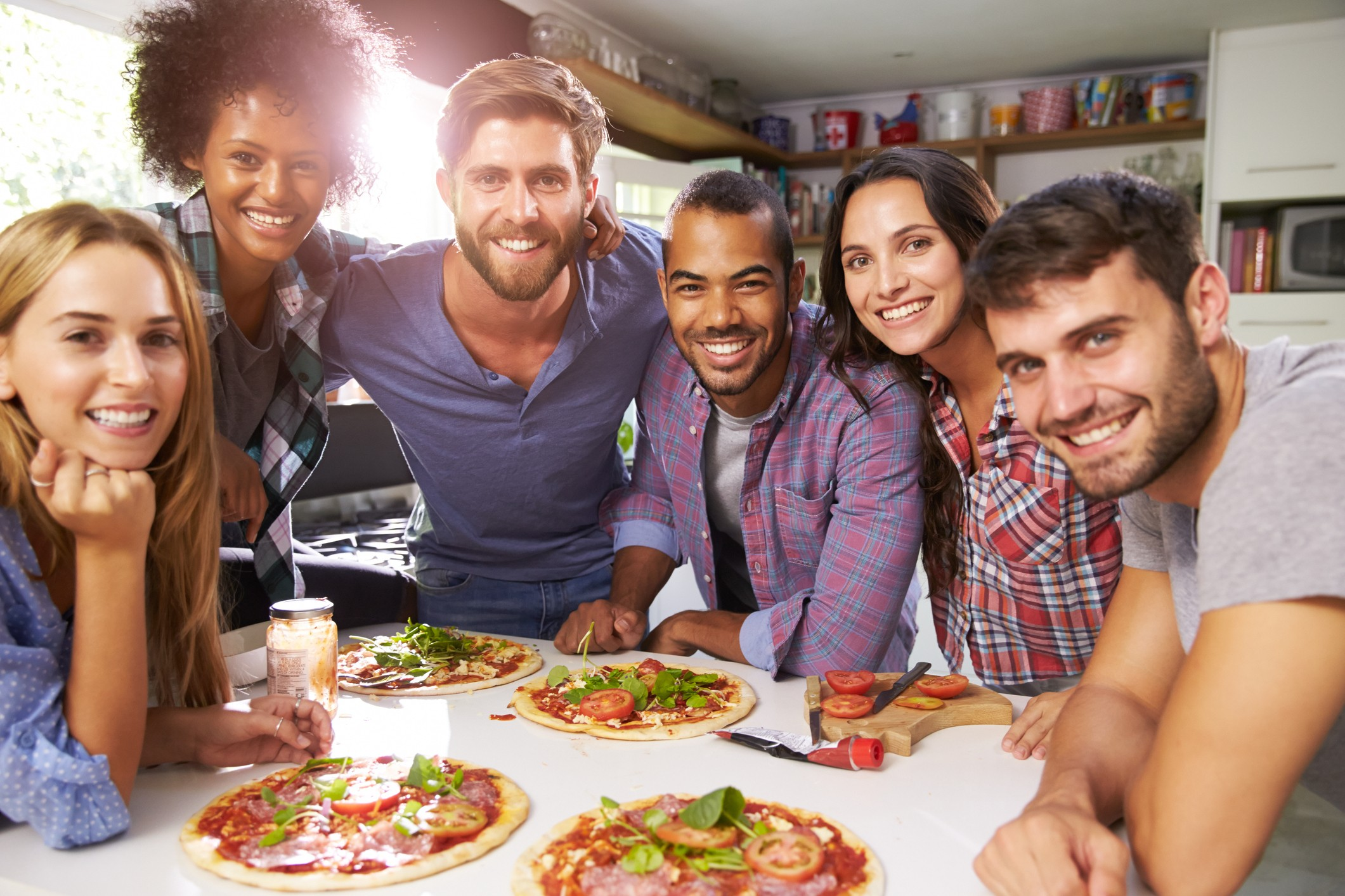 group of roommates making pizza