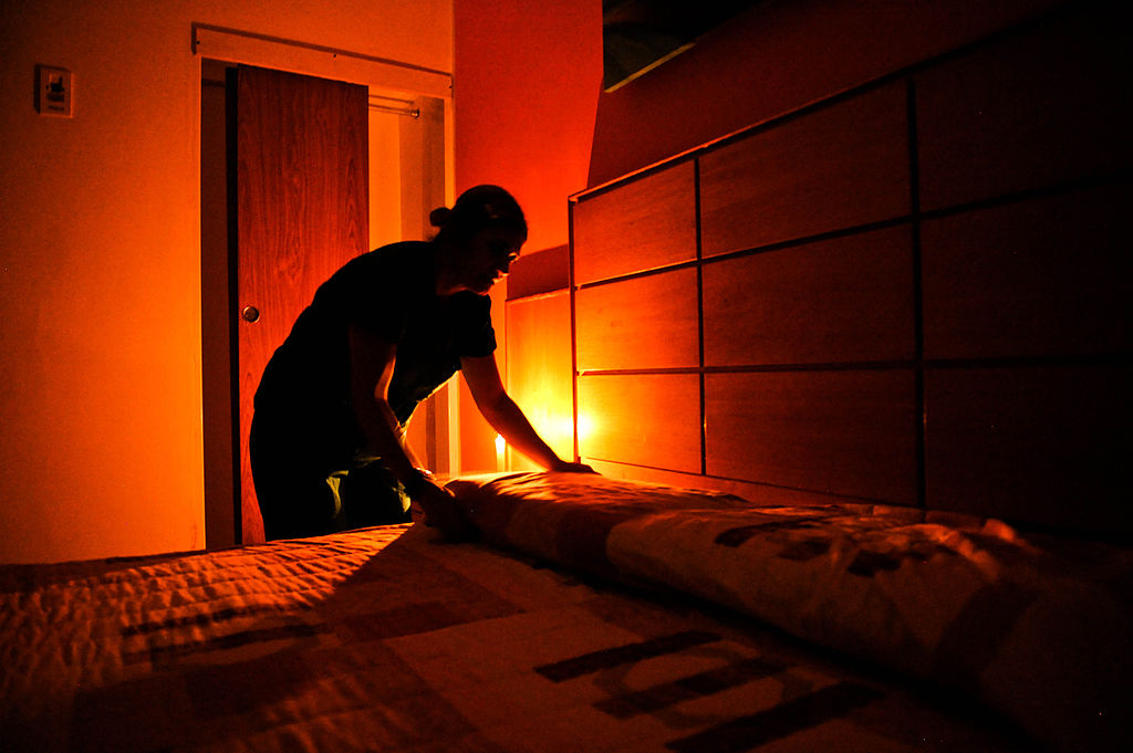 A chambermaid makes a bed at a hotel
