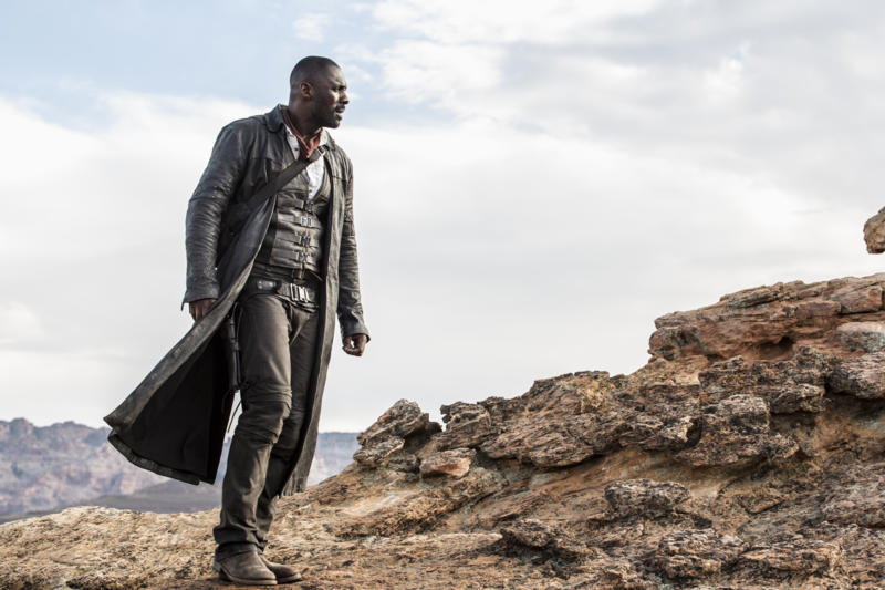 Idris Elba in a black leather duster looking out over rocks