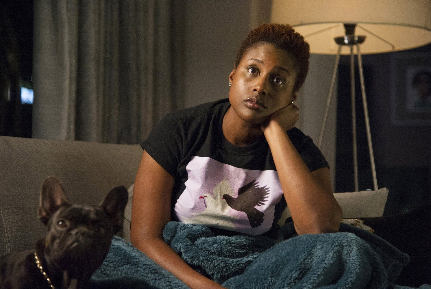Issa Rae with her head resting on her hand sitting on a couch next to a French Bull Dog
