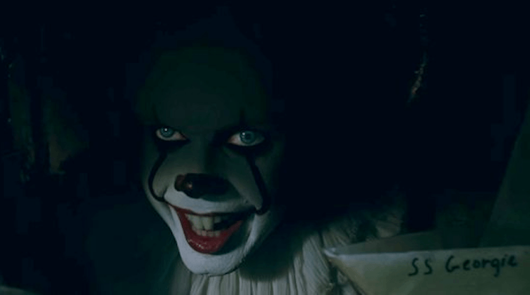 Pennywise the Clown peeks out from the sewer holding a paper boat