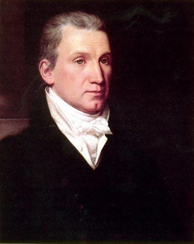 James Monroe posing in front of a dark background and wearing a black coat.