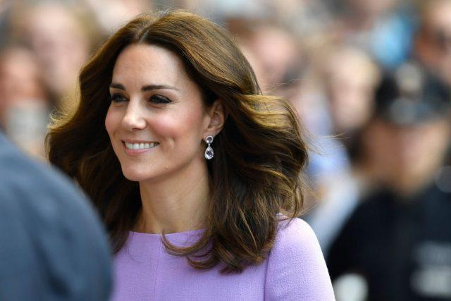 Kate Middleton smiles as her hair blows in the wind.